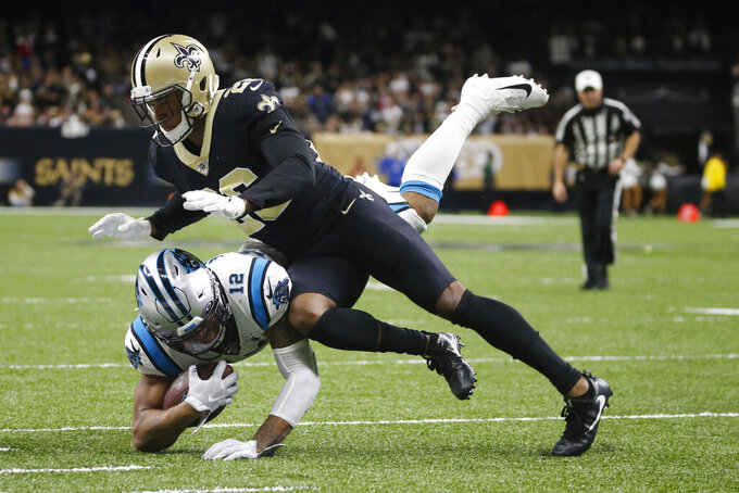 New Orleans Saints cornerback P.J. Williams (26) brings down Carolina Panthers wide receiver D.J. Moore (12), during the second half at an NFL football game, Sunday, Nov. 24, 2019, in New Orleans. (AP Photo/Butch Dill)