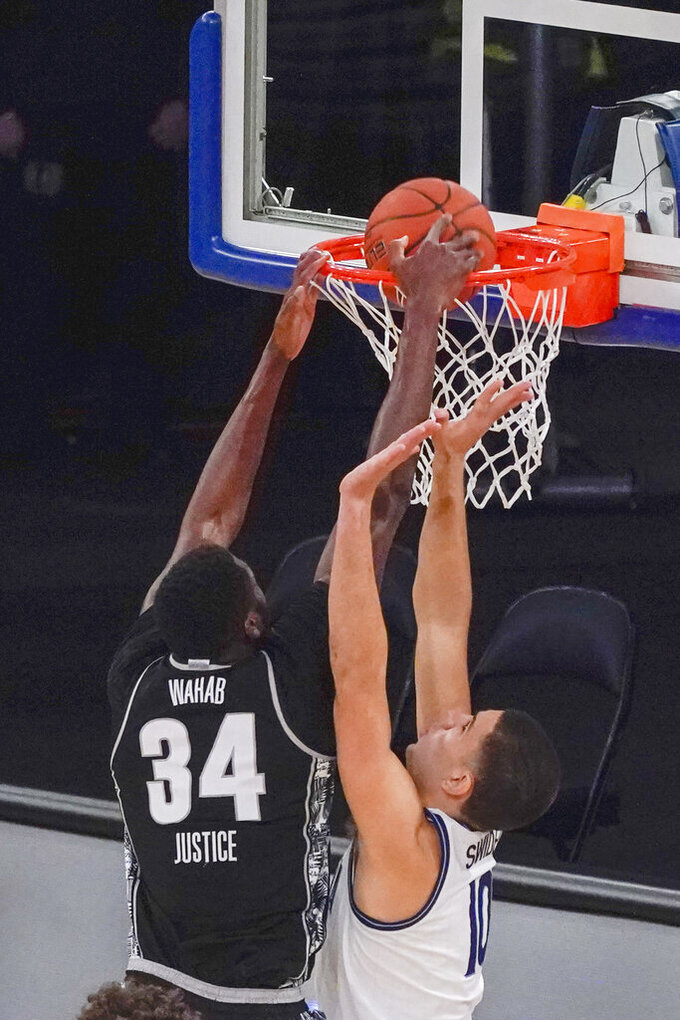 Georgetown center Qudus Wahab (34) dunks past Villanova forward Cole Swider (10) during the second half of an NCAA college basketball game in the quarterfinals of the Big East conference tournament, Thursday, March 11, 2021, in New York. Georgetown won 72-71. (AP Photo/Mary Altaffer)