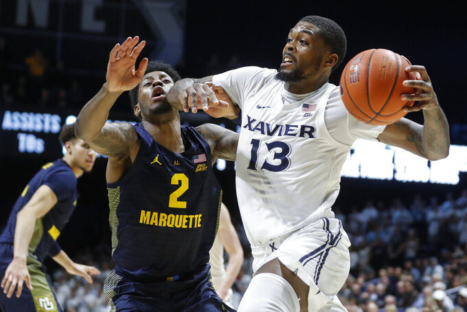 Xavier'd Naji Marshall (13) fouls Marquette's Sacar Anim (2) on a drive during the second half of an NCAA college basketball game Wednesday, Jan. 29, 2020, in Cincinnati. (AP Photo/John Minchillo)
