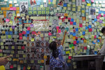 In this photo taken Friday, July 12, 2019, a child reaches out to post-it notes on the city's version of the Lennon Wall in Hong Kong. Hong Kong activists first created their own Lennon Wall during the 2014 protests, covering a wall with a vibrant Post-it notes calling for democratic reform. This time, they have taken to sticking the neon-colored notes everywhere, erecting impromptu Lennon Walls across the city as quickly as others might tear them down. Some protesters have called it
