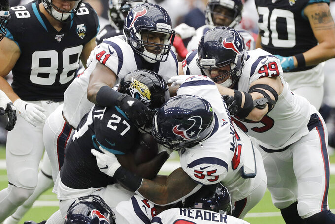 Jacksonville Jaguars running back Leonard Fournette (27) is stopped by Houston Texans inside linebacker Benardrick McKinney (55) and inside linebacker Zach Cunningham (41) during the first half of an NFL football game Sunday, Sept. 15, 2019, in Houston. (AP Photo/David J. Phillip)