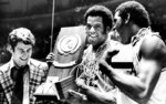 FILE - In this March 30, 1976, file photo, Indiana coach Bobby Knight, left, and team members Scott May, center, and Quinn Buckner, right, celebrate with the trophy after winning the NCAA Basketball Championship in Philadelphia. They beat Michigan 86-68. The Indiana Hoosiers sat quietly inside their locker room on March 22, 1975. They knew what the first and only loss that season signified — one perfect quest ended while another began. Minutes after losing 92-90 to archrival Kentucky in the Mideast Regional championship, the underclassmen vowed to come back the next season and go undefeated. They did. And 45 years later, the 1975-76 Hoosiers remain America's last perfect college basketball team.  (AP Photo/File)