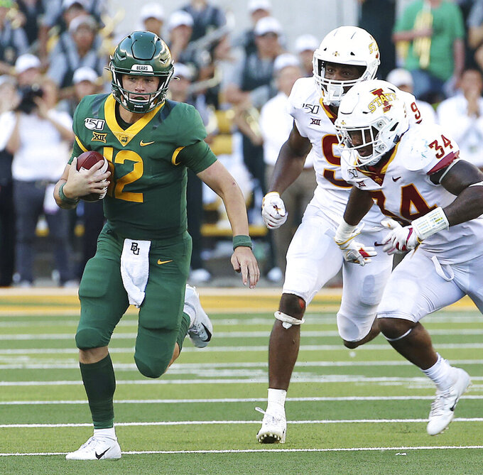 Baylor quarterback Charlie Brewer, left, runs for a first down past Iowa State linebacker O'Rien Vance, right, in the second half of an NCAA college football game, Saturday, Sept. 28, 2019, in Waco, Texas.  (Jerry Larson/Waco Tribune-Herald via AP)