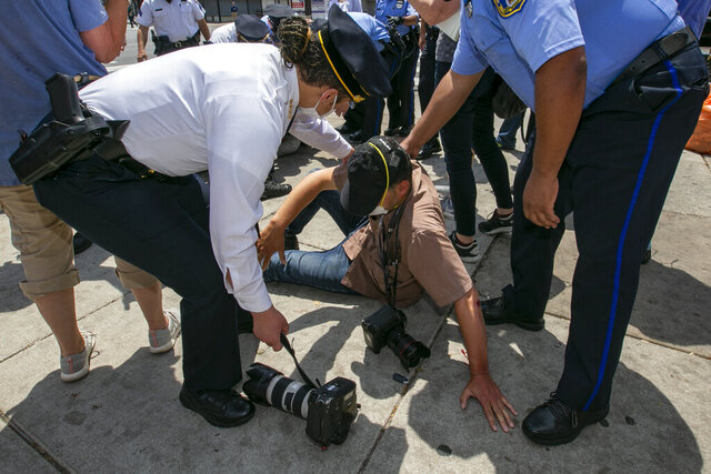 Police Commissioner Danielle Outlaw, left, and other officers attend to Associated Press photographer Matt Rourke after he was assaulted while touring the business district with Philadelphia Mayor Jim Kenney and police officers at N. Broad Street and Erie Avenue in Philadelphia on Thursday, June 4, 2020. (Alejandro A. Alvarez/The Philadelphia Inquirer via AP)