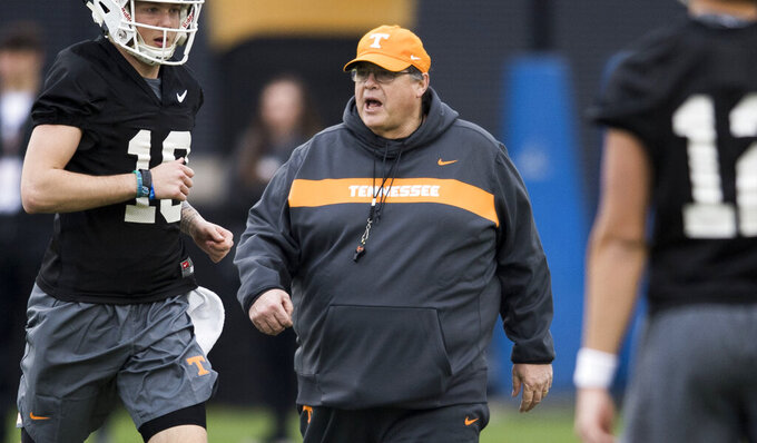 FILE - In this March 7, 2019, file photo, Tennessee offensive coordinator Jim Chaney walks on the field during Tennessee football's first practice of the spring season in Knoxville, Tenn. Chaney exemplifies the nomadic nature of an SEC coordinator. He's back for his second stint as Tennessee's offensive coordinator after holding the same title at Arkansas, Pittsburgh and Georgia since his last stay in Knoxville. (Caitie McMekin/Knoxville News Sentinel via AP, File)