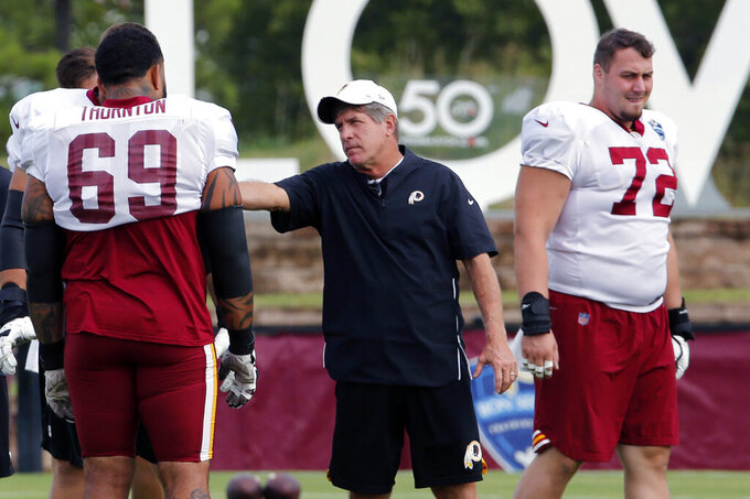 FILE - In this Aug. 5, 2019, file photo, Washington Redskins offensive line coach Bill Callahan, center, talks with tackle Hugh Thornton (69) during NFL football training camp in Richmond, Va. Jay Gruden was fired as head coach of the Washington Redskins on Monday, Oct. 7, 2019, after an 0-5 start to the sixth season of a tenure that featured only one playoff appearance. A person familiar with the team's plans told The Associated Press that offensive line coach Bill Callahan would replace Gruden on an interim basis. (AP Photo/Steve Helber, File)