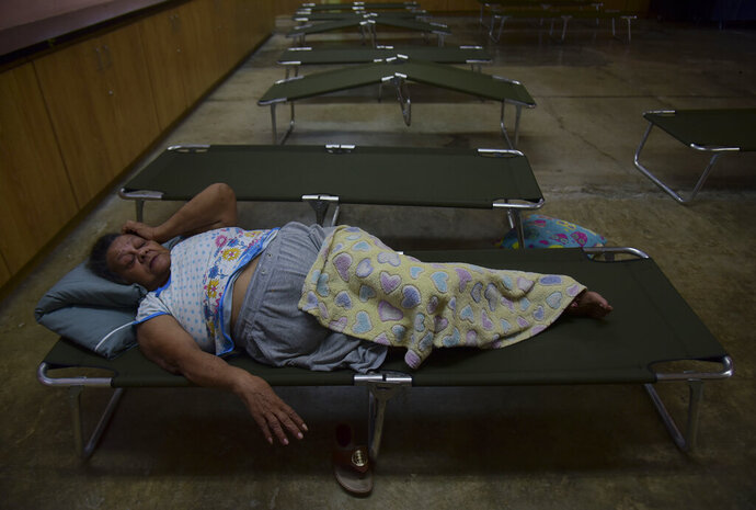 Luz Aponte Velazquez lies on a cot at the Ramon Quinones Medina High School, one of the shelters enabled by the municipality of Yabucoa, before the arrival of Tropical Storm Karen, in Yabucoa, Puerto Rico, Tuesday, Sept. 24, 2019. Tropical Storm Karen regained strength as it swirled toward Puerto Rico, where it's expected to bring heavy rains and strong winds. (AP Photo/Carlos Giusti)