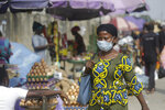 A woman wearing a face mask to protect against coronavirus, walks on a street, in Lagos, Nigeria , Thursday, Dec. 31, 2020. A Nigerian scientist has spent the holiday season in his laboratory doing genetic sequencing to learn more about the country's COVID-19 variant, as cases increase in the country. Virologist Sunday Omilabu says the information he gathers about the variant will help battle the spread of the disease in Nigeria, Africa's most populous country with 196 million people. (AP Photo/Sunday Alamba)