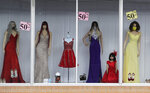 Sale signs are posted on a display window with mask covered mannequins at a dress shop, Thursday, July 30, 2020, in McAllen,Texas. (AP Photo/Eric Gay)