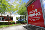 FILE - In this July 1, 2019, file photo, a help wanted sign appears on a bus stop in front of a McDonald's restaurant in Miami. On Tuesday, Feb. 11, 2020, the Labor Department reports on job openings and labor turnover for December. (AP Photo/Wilfredo Lee, File)
