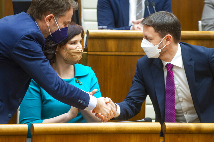 Slovakia Prime Minister Eduard Heger, right, shakes hands with vice-premier and Minister of Finance Igor Matovic, left, and vice-premier Veronika Remisova, center, after surviving a vote of confidence in Bratislava, Tuesday May 4, 2021.  Eduard Heger's Cabinet obtained a vote of confidence from Parliament on Tuesday. (Jakub Kotian / TASR via AP)