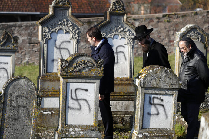 French Interior Minister Christophe Castaner, center, followed by Strasbourg chief Rabbi Harold Abraham Weill, second right, walk amid vandalized tombs in the Jewish cemetery of Westhoffen, west of the city of Strasbourg, eastern France, Wednesday, Dec. 4, 2019. Regional authorities in eastern France say vandals have scrawled anti-Semitic inscriptions, including swastikas spray-painted in black, on 107 tombs in a Jewish cemetery. (AP Photo/Jean-Francois Badias)