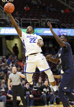 Buffalo's Dontay Caruthers (22) drives to the basket against Akron's Deng Riak (10) during the first half of an NCAA college basketball game in the Mid-American Conference tournament, Thursday, March 14, 2019, in Cleveland. (AP Photo/Tony Dejak)