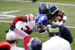 Seattle Seahawks running back Chris Carson (32) is stopped by New York Giants cornerback Darnay Holmes (30) during the second half of an NFL football game, Sunday, Dec. 6, 2020, in Seattle. (AP Photo/Elaine Thompson)