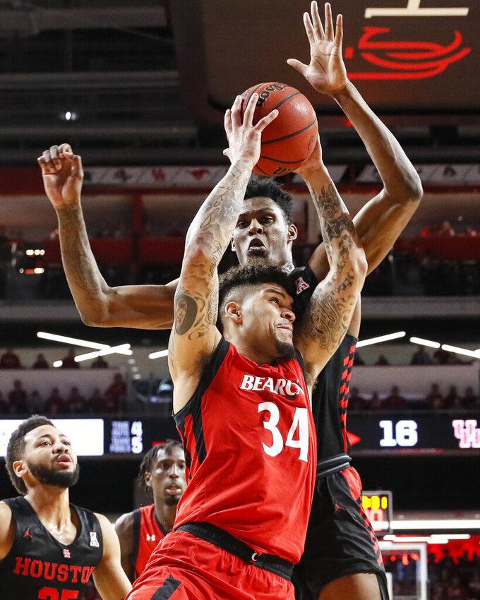 Cincinnati's Jarron Cumberland (34) shoots against Houston's Chris Harris Jr., top2, in the first half of an NCAA college basketball game, Sunday, March 10, 2019, in Cincinnati. (AP Photo/John Minchillo)