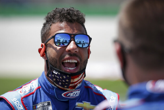 Bubba Wallace talks to a crew member before the start of a NASCAR Cup Series auto race Sunday, July 12, 2020, in Sparta, Ky. (AP Photo/Mark Humphrey)