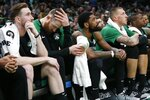 Boston Celtics' Gordon Hayward, Aron Baynes, Kyrie Irving and Daniel Theis, from left, sit on the bench during the second half of the team's NBA basketball game against the San Antonio Spurs in Boston, Sunday, March 24, 2019. (AP Photo/Michael Dwyer)