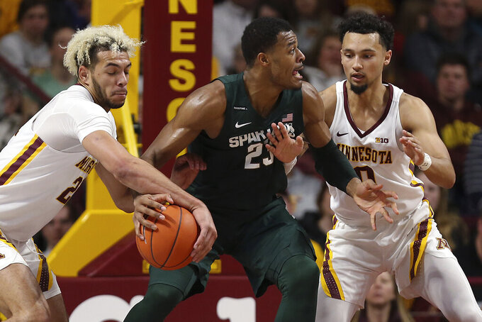 Minnesota's Jarvis Omersa, left, steals the ball from Michigan State's Xavier Tillman during an NCAA college basketball game Sunday, Jan. 26, 2020, in Minneapolis. (AP Photo/Stacy Bengs)