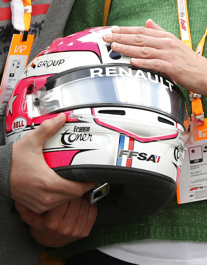The mother and brother of Anthoine Hubert hold the helmet of Formula 2 driver Anthoine Hubert during a moment of silence at the Belgian Formula One Grand Prix circuit in Spa-Francorchamps, Belgium, Sunday, Sept. 1, 2019. The 22-year-old Hubert died following an estimated 160 mph (257 kph) collision on Lap 2 at the high-speed Spa-Francorchamps track, which earlier Saturday saw qualifying for Sunday's Formula One race. (AP Photo/Francisco Seco)