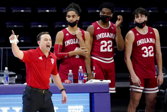 Indiana coach Archie Miller, left, yells to the team as guard Khristian Lander (4), forward Jordan Geronimo (22), and guard Trey Galloway (32) stand near the court during the second half of an NCAA college basketball game against Northwestern in Evanston, Ill., Wednesday, Feb. 10, 2021. (AP Photo/Nam Y. Huh)
