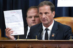 Rep. Chris Stewart, R-Utah, holds up a copy of the transcript of a phone call between President Donald Trump and Ukrainian President Volodymyr Zelenskiy during the House Intelligence Committee on Capitol Hill in Washington, Wednesday, Nov. 13, 2019, in the first public impeachment hearing of President Donald Trump's efforts to tie U.S. aid for Ukraine to investigations of his political opponents.  (Saul Loeb/Pool Photo via AP)