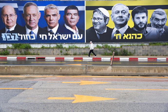 An Ultra-Orthodox Jewish man looks at an elections billboards of the Blue and White party leaders, from left to right, Moshe Yaalon, Benny Gantz, Yair Lapid and Gabi Ashkenazi, alongside a panel on the right showing Prime Minister Benjamin Netanyahu flanked by extreme right politicians, from the left, Itamar Ben Gvir, Bezalel Smotrich and Michael Ben Ari in Bnei Brak, Israel, Saturday, March 16, 2019. Hebrew reads on the left billboard
