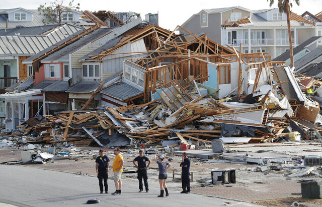 FILE - In this Thursday, Oct. 11, 2018. file photo, rescue personnel perform a search in the aftermath of Hurricane Michael in Mexico Beach, Fla.  Officials in in Mexico Beach are hoping tourists will help rebuild the neighboring beach town devastated by Hurricane Michael in 2018. Officials in Panama City Beach on Tuesday, Jan. 14, 2020 introduced a program that allows tourists during their visit to help build homes and plant sea oats in the sand dunes of neighboring Mexico Beach, which was demolished by the category 5 storm. (AP Photo/Gerald Herbert, File)