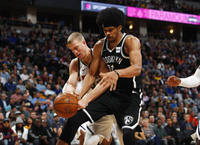 Brooklyn Nets center Jarrett Allen, front, fights for control of a rebound with Denver Nuggets center Mason Plumlee in the second half of an NBA basketball game Thursday, Nov. 14, 2019, in Denver. The Nuggets won 101-93. (AP Photo/David Zalubowski)
