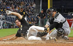 Pittsburgh Pirates' Adam Frazier, left, beats the tag by Chicago White Sox catcher Welington Castillo to score from first on a double off the center field wall by Pittsburgh Pirates' Gregory Polanco during the sixth inning of a baseball game in Pittsburgh, Tuesday, May 15, 2018. (AP Photo/Gene J. Puskar)