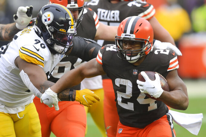 Cleveland Browns running back Nick Chubb (24) rushes against Pittsburgh Steelers defensive end Isaiah Buggs (96) during the first half of an NFL football game, Sunday, Jan. 3, 2021, in Cleveland. (AP Photo/David Richard)