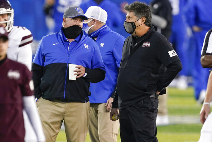 Kentucky coach Mark Stoops and Mississippi State coach Mike Leach, right, talk before an NCAA college football game Saturday, Oct. 10, 2020, in Lexington, Ky. (AP Photo/Bryan Woolston)