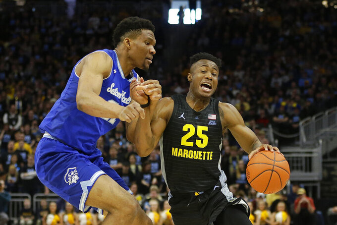 Marquette's Koby McEwen (25) drives to the basket against Seton Hall's Ike Obiagu during the first half of an NCAA college basketball game Saturday, Feb. 29, 2020, in Milwaukee. (AP Photo/Aaron Gash)