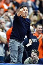 Jimmy Fallon stands on his chair as he is introduced to the crowd during the first half of an NCAA college basketball game between Syracuse and North Carolina in Syracuse, N.Y., Saturday, Feb. 29, 2020. (AP Photo/Adrian Kraus)