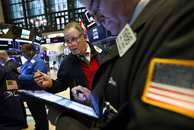 Michael Conlon, center, works with fellow traders on the floor of the New York Stock Exchange, Thursday, March 12, 2020. Stocks are sharply lower after resuming trading as traders fear that not enough is being done to contain the economic damage from the coronavirus pandemic. (AP Photo/Richard Drew)
