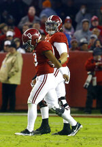 Alabama quarterback Tua Tagovailoa (13) is helped off the field by offensive lineman Jedrick Wills Jr. (74) during the second half of an NCAA college football game against Mississippi State, Saturday, Nov. 10, 2018, in Tuscaloosa, Ala.  (AP Photo/Butch Dill)