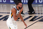 Utah Jazz's Rudy Gobert (27) reaches up after being hit in the face during play against the Denver Nuggets during the second half an NBA first round playoff basketball game, Tuesday, Sept. 1,2020, in Lake Buena Vista, Fla. (AP Photo/Mark J. Terrill)