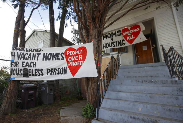 FILE - In this Jan. 14, 2020, file photo, signs are posted outside of a house was occupied by the group Moms 4 Housing in Oakland, Calif. The mayor of Berkeley is proposing a new housing policy law Thursday, Feb. 20, 2020, aimed at giving renters first dibs when a property goes up for sale as the state battles a severe housing shortage and homeless crisis that Gov. Gavin Newsom has declared his top priority. (AP Photo/Jeff Chiu, File)
