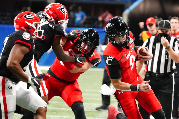 Cincinnati quarterback Desmond Ridder (9) runs against Georgia during the first half of the Peach Bowl NCAA college football game, Friday, Jan. 1, 2021, in Atlanta. (AP Photo/Brynn Anderson)