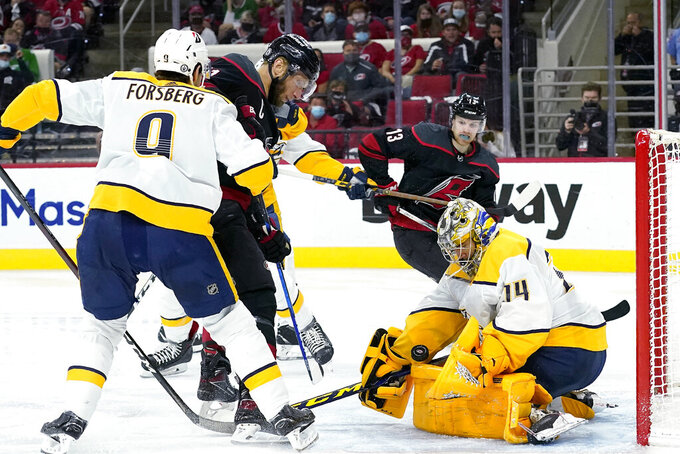 Nashville Predators left wing Filip Forsberg (9) and goaltender Juuse Saros (74) block Carolina Hurricanes center Jordan Staal as Hurricanes left wing Warren Foegele (13) watches during the second period in Game 5 of an NHL hockey Stanley Cup first-round playoff series in Raleigh, N.C., Tuesday, May 25, 2021. (AP Photo/Gerry Broome)