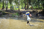 A woman carrying belongings on her head wades across the shallow Lubiriha River, an area that is popular with those who want to cross into Uganda without passing through the official border crossing, in Kasindi, eastern Congo Wednesday, June 12, 2019, just across the border from the Ugandan town of Bwera. In Uganda, a 5-year-old boy vomiting blood became the first cross-border victim of Ebola in the current outbreak on Wednesday, while two more people in Uganda tested positive for the highly contagious disease that has killed nearly 1,400 in Congo. (AP Photo/Al-hadji Kudra Maliro)