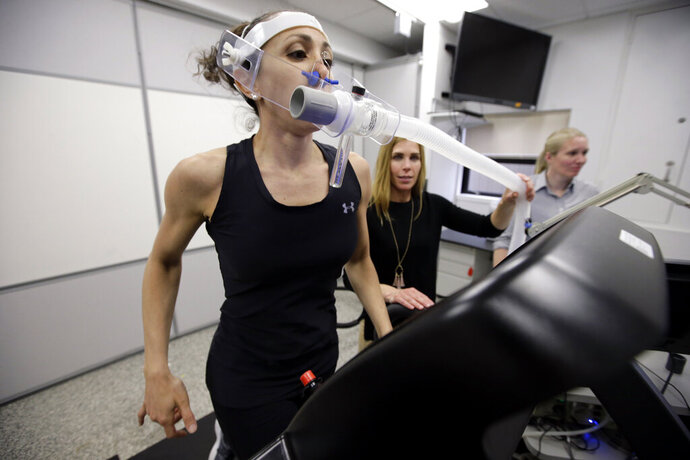 In this April 23, 2019 photo, research scientist Leila Walker, left, is assisted by nutritional physiologist Holly McClung, center, as they demonstrate equipment designed to evaluate fitness levels in female soldiers, not shown, who have joined elite fighting units such the Navy Seals, at the U.S. Army Research Institute of Environmental Medicine, at the U.S. Army Combat Capabilities Development Command Soldier Center, in Natick, Mass. (AP Photo/Steven Senne)
