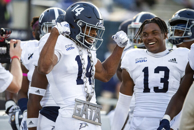 Georgia Southern cornerback Darrell Baker Jr. (14) celebrates on the sideline after intercepting a pass during the second half of an NCAA football game against Massachusetts, Saturday, Oct. 17, 2020, in Statesboro, Ga. (AP Photo/Stephen B. Morton)