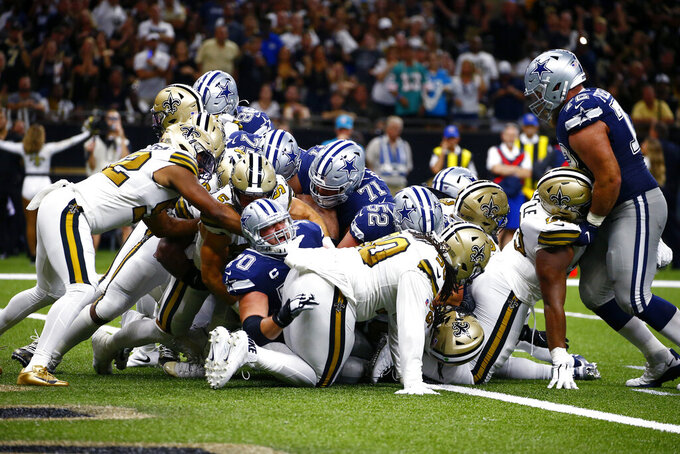 Dallas Cowboys offensive guard Zack Martin (70) yells from the pile as running back Ezekiel Elliott, not pictured, crosses the goal line for a touchdown in the second half of an NFL football game against the New Orleans Saints in New Orleans, Sunday, Sept. 29, 2019. (AP Photo/Butch Dill)