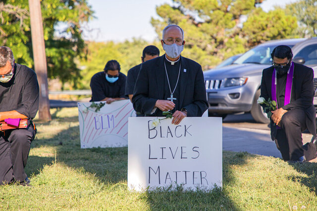 In this June 1, 2020, photo provided by the Catholic Diocese of El Paso, Bishop Mark Seitz, center, kneels with other demonstrators at Memorial Park holding a Black Lives Matter sign in El Paso, Texas. Pope Francis called Seitz unexpectedly after he was photographed at the protest. (Fernie Ceniceros/Catholic Diocese of El Paso via AP)