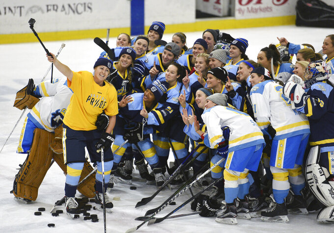 """FILE - In this Sunday, Jan. 24, 2016, file photo, National Women's Hockey League All-Star players take time for a """"selfie"""" before an all-star game at Harborcenter in Buffalo, N.Y. The National Women's Hockey League is adding a seventh team by expanding into Montreal next season, two people with direct knowledge of the league's board of governors' approved plan told The Associated Press. The people spoke to The AP on the condition of anonymity because they are not authorized to speak for the NWHL. League spokesman, Paul Krotz, would only say the NWHL had """"nothing to report regarding season seven expansion,"""" in an email sent late Monday, March 22, 2021.  (AP Photo/Gary Wiepert, File)"""