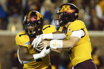 Minnesota quarterback Tanner Morgan, right, hands off the ball to running back Rodney Smith (1) during the first half of an NCAA college football game against South Dakota State, Thursday, Aug. 29, 2019, in Minneapolis. (AP Photo/Stacy Bengs)