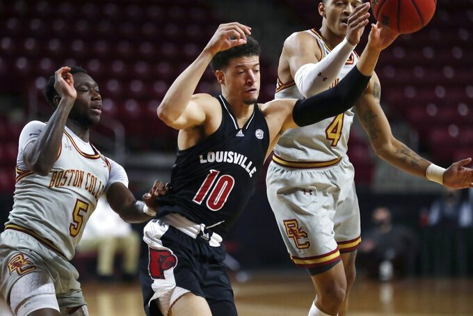 Boston College's Makai Ashton-Langford (4) and Jay Heath (5) battle Louisville's Samuell Williamson (10) for a rebound during the first half of an NCAA college basketball game, Saturday, Jan. 2, 2021, in Boston. (AP Photo/Michael Dwyer)