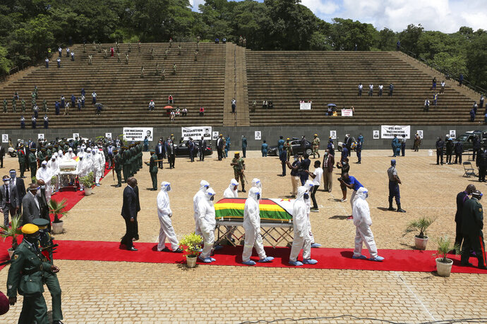 Pallbearers carry the coffin of a government minister of Dr Ellen Gwaradzimba who died of COVID-19, at the Heroes Acre in Harare, Thursday, Jan. 21, 2021. Zimbabwean President Emmerson Mnangagwa who presided over the burial called the pandemic