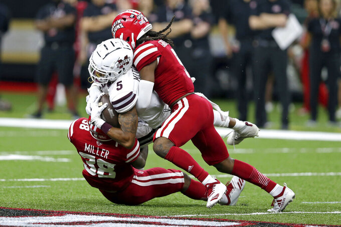 Mississippi State wide receiver Osirus Mitchell (5) is tackled by Louisiana-Lafayette defensive backs Terik Miller (38) and Kamar Greenhouse (9) during the first quarter of an NCAA college football game in New Orleans, Saturday, Aug. 31, 2019. (AP Photo/Chuck Cook)