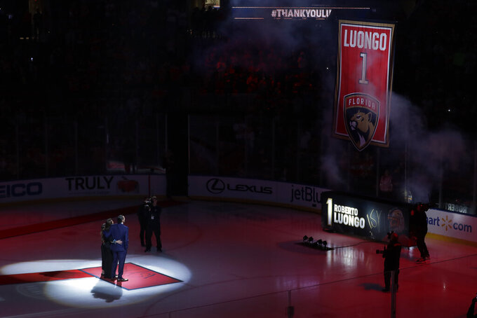 Former Florida Panthers goalie Roberto Luongo, left, and his family watch as his jersey is hoisted to the rafters during a ceremony before an NHL hockey game against the Montreal Canadiens, Saturday, March 7, 2020, in Sunrise, Fla. (AP Photo/Wilfredo Lee)
